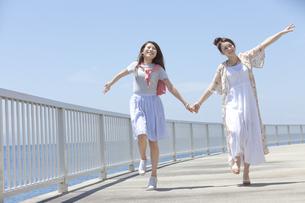 手をつないで走る女性2人の写真素材 [FYI01327571]