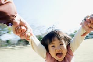 回転遊びで宙を舞う日本人の女の子の笑顔の写真素材 [FYI01327601]