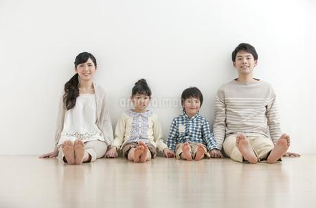 フローリングに座る家族4人の写真素材 [FYI01328049]