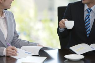 打ち合わせをするビジネスマンとビジネスウーマンの手元の写真素材 [FYI01328051]