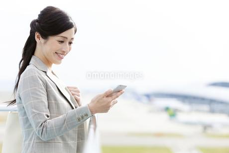 スマートフォンを持つビジネスウーマンの写真素材 [FYI01328090]
