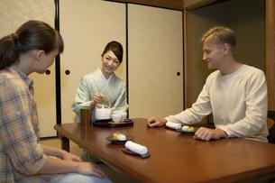 お茶を注ぐ日本人女性と外国人カップルの写真素材 [FYI01328123]