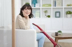 掃除機を持って座る女性の写真素材 [FYI01328230]
