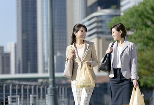 コンビニ袋を持つビジネスウーマン2人の写真素材 [FYI01328263]