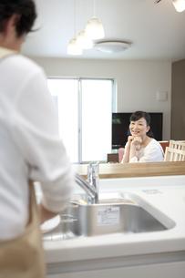 皿洗いをする男性を見ている女性の写真素材 [FYI01328286]