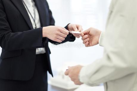 名刺を交換するビジネスマンとビジネスウーマンの写真素材 [FYI01329237]