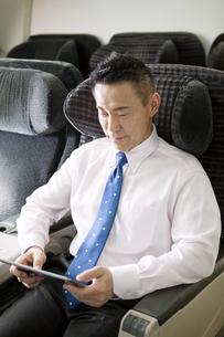 機内でタブレットPCを見るビジネスマンの写真素材 [FYI01330087]