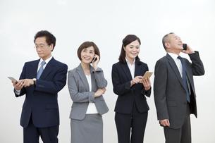スマートフォンを持つビジネスグループ4人の写真素材 [FYI01330243]