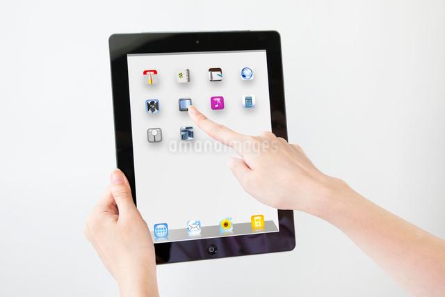 タブレット型コンピューターを操作する女性の手の写真素材 [FYI01330437]