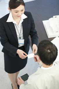 名刺を交換するビジネスマンとビジネスウーマンの写真素材 [FYI01330440]