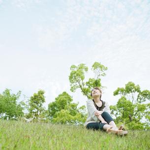 草原に座って空を見上げる女性の写真素材 [FYI01330703]