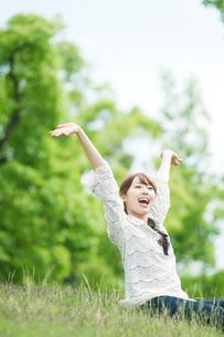 草原に座って伸びをする女性の写真素材 [FYI01331512]