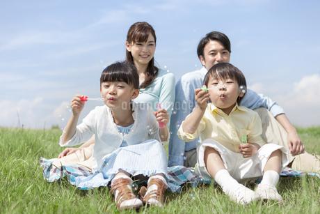シャボン玉で遊ぶ家族4人の写真素材 [FYI01332105]