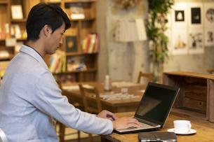 カフェでノートパソコンを操作する男性の写真素材 [FYI01332249]