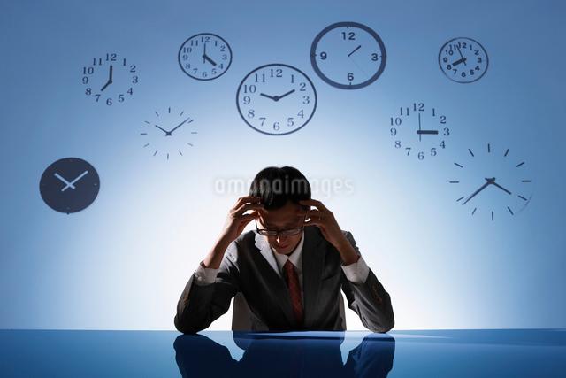 時計の背景の前で悩むビジネスマンの写真素材 [FYI01333386]