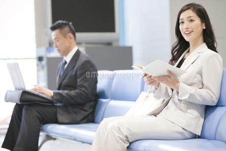 待合室で本を読むビジネスウーマンの写真素材 [FYI01333438]