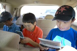 車の中でゲームをする少年達の写真素材 [FYI01333635]