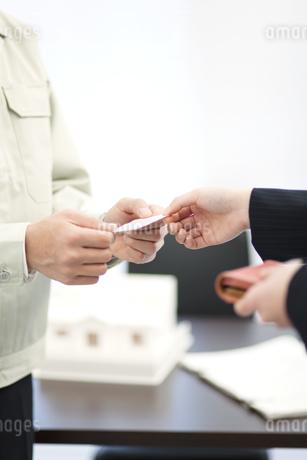 名刺を交換するビジネスマンとビジネスウーマンの写真素材 [FYI01334174]