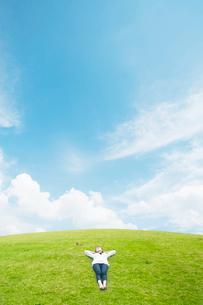 草原で寝転ぶ女性の写真素材 [FYI01335288]