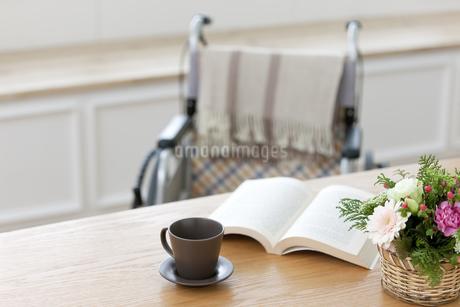 テーブルに置かれた本と車椅子の写真素材 [FYI01335294]
