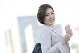 スマートフォンで音楽を聴くビジネスウーマンの写真素材 [FYI01335302]
