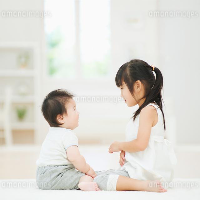 泣きそうな赤ちゃんを見つめる女の子の写真素材 [FYI01335908]