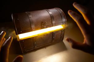 光輝く宝箱を見つけた男性の手の写真素材 [FYI01335987]
