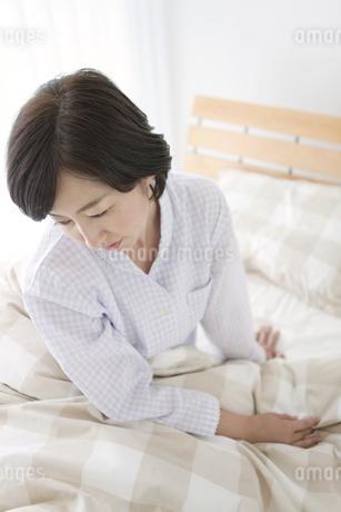 ベッドに座る中高年女性の写真素材 [FYI01336039]