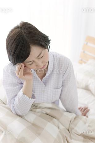 ベッドでこめかみを押さえる中高年女性の写真素材 [FYI01336140]