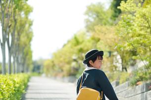 新緑の歩道を歩く幼稚園児の男の子の写真素材 [FYI01336178]