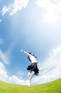 草原でジャンプする女の子の写真素材 [FYI01336483]