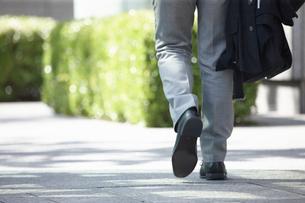 オフィス街を歩き信号待ちをするサラリーマンの足元の写真素材 [FYI01336613]