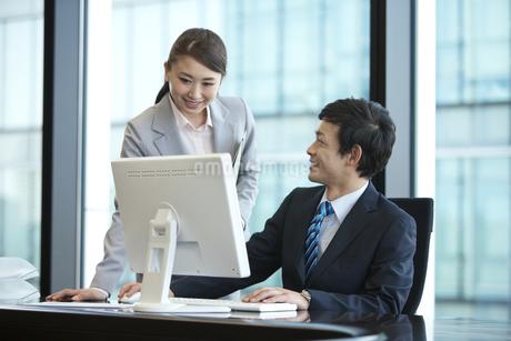パソコンを見るビジネスマンとビジネスウーマンの写真素材 [FYI01337217]