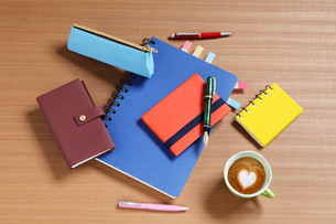 机の上のノートと万年筆とハートマークのコーヒーの写真素材 [FYI01337362]
