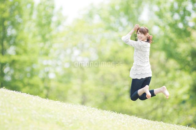新緑の中をジャンプする女性の写真素材 [FYI01337597]