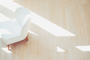 日差し差すフローリングに置いてある白い椅子の写真素材 [FYI01338251]