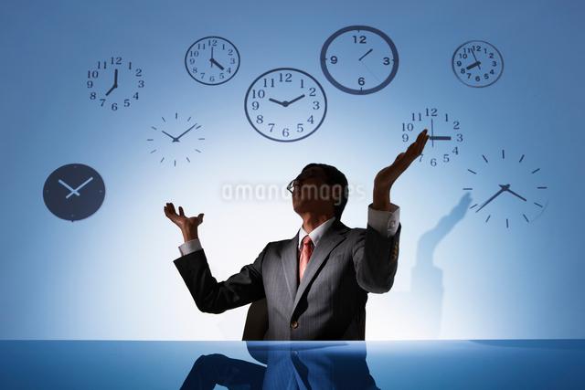 時計の背景の前で諦めたお手上げなビジネスマンの写真素材 [FYI01338273]