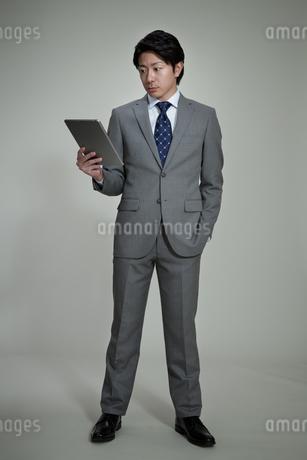 タブレットPCを見るビジネスマンの写真素材 [FYI01338659]