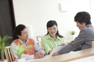 ビジネスマンの説明を聞く中高年夫婦の写真素材 [FYI01339203]