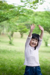 林の中で手を上げて笑う女の子の写真素材 [FYI01339974]