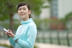 ジョギング姿でスマートフォンを持つ女性の写真素材 [FYI01340509]