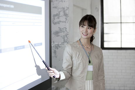 プロジェクターで説明するビジネス女性の写真素材 [FYI01340540]