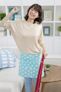掃除機を持って伸びをする女性の写真素材 [FYI01340565]