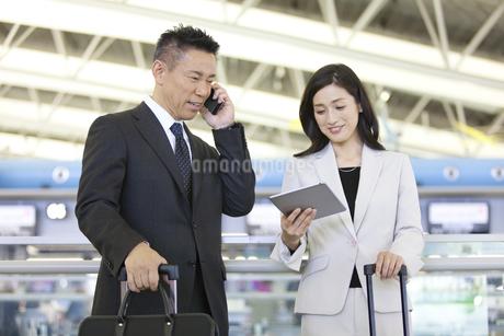 タブレットPCを持つビジネスウーマンと電話するビジネスマンの写真素材 [FYI01340682]