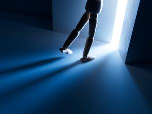 暗闇の中から扉を開けて光に向かう人形の足の写真素材 [FYI01342593]