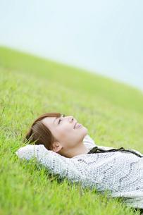 草原で寝転ぶ女性の写真素材 [FYI01342951]