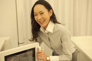 電子レンジを開ける女性の写真素材 [FYI01343467]