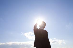 太陽に手をかざすビジネスマンの写真素材 [FYI01344058]