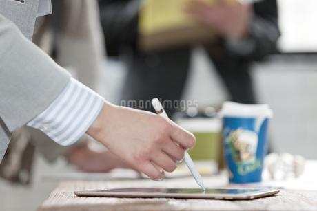 タブレットPCを操作するビジネス女性の手元の写真素材 [FYI01344554]