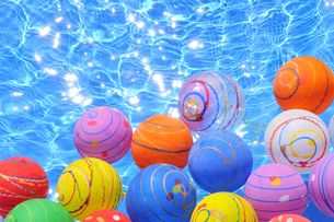 水に浮くカラフルなヨーヨーの写真素材 [FYI01344672]